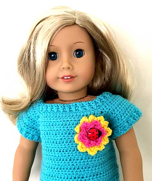 Jersey para muñeca en crochet decorado con un botón en forma de mariquita