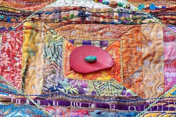 Quilt decorado con un botón grande y abalorios variados