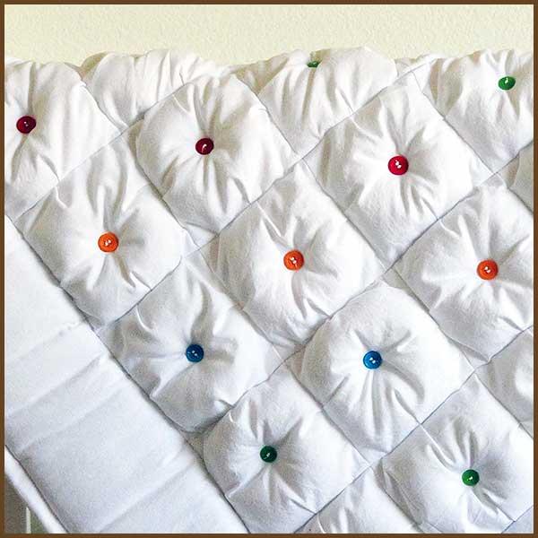 colcha blanca con botones de colores