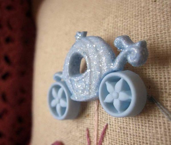 Detalle del cojín con botón en forma de carroza de Cenicienta