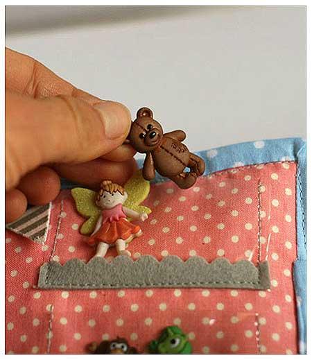 Botón con forma de osito usado como juguete en libro de tela