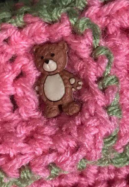 Botón con forma de osito colocado en prenda de lana