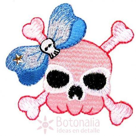Calavera rosa con tibias y un lazo azul.